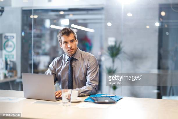 pensive entrepreneur working on laptop in the office. - economist stock pictures, royalty-free photos & images