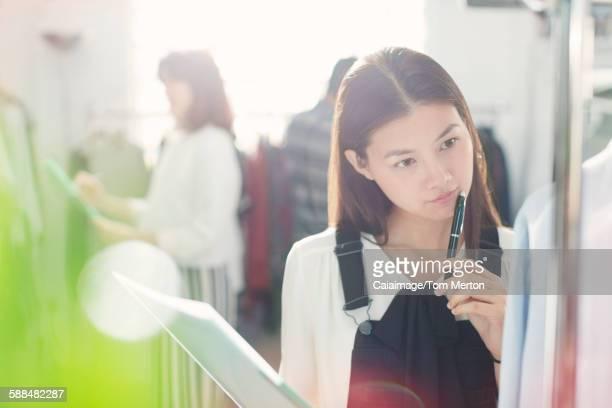 Pensive fashion designer examining shirt