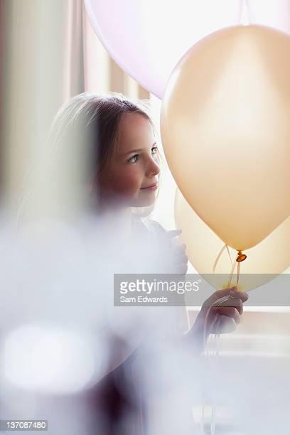 Pensive girl holding white balloons