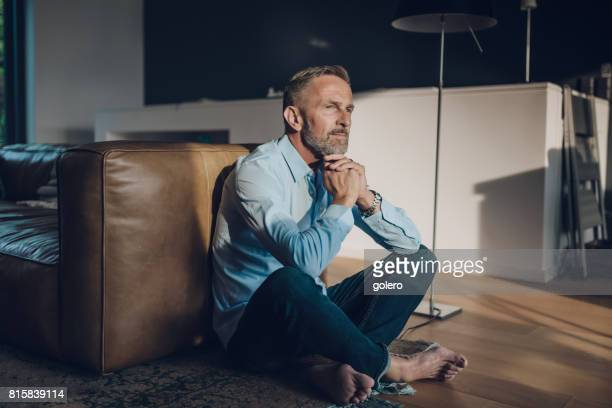 pensive handsome bearded midaged man sitting on floor