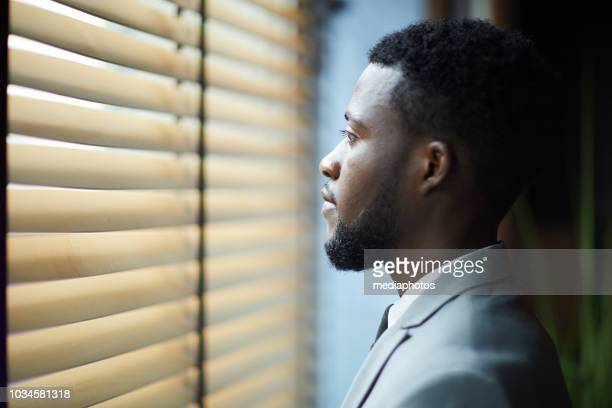 pensive handsome young african man with beard looking through blinds while thinking about new project in corridor - one man only stock pictures, royalty-free photos & images