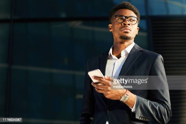 pensive handsome young afro-american businessman with beard using modern gadget on move - formal stock pictures, royalty-free photos & images