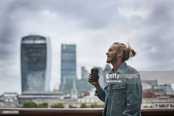 pensive hipster drinking coffee in the street at london - jonge mannen stockfoto's en -beelden