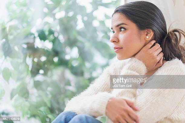 Pensive Hispanic woman looking out window