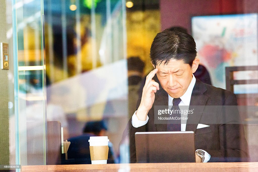 Pensive Japanese man in cafe trying to remember important information : Stock Photo