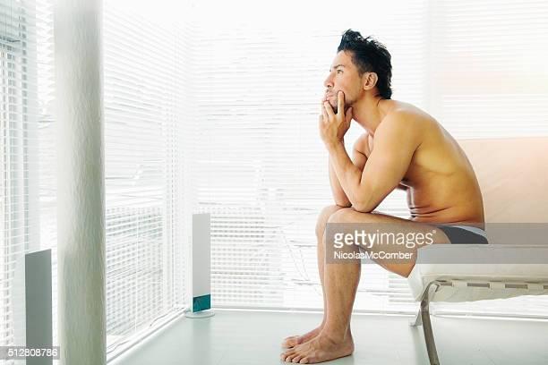 日本を置く哀愁漂う男性下着哀愁自身のリビングルームです。 - セミヌード ストックフォトと画像