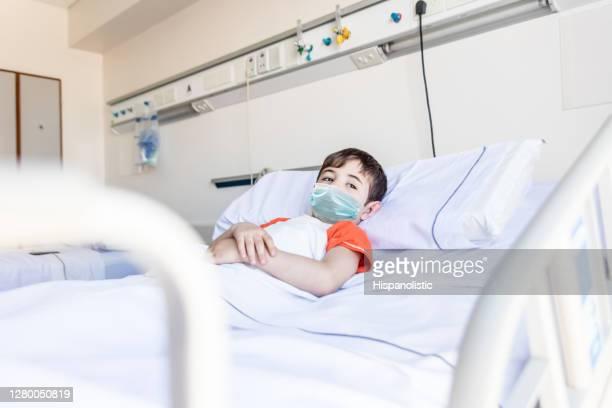 peinzend weinig jongen die op het ziekenhuisbed ligt dat weg met droefheid weg kijkt die een beschermend gezichtsmasker draagt - alleen jongens stockfoto's en -beelden