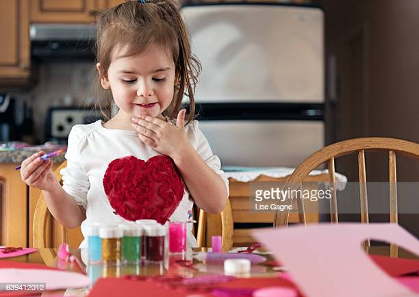Pensive little girl creating bricolage