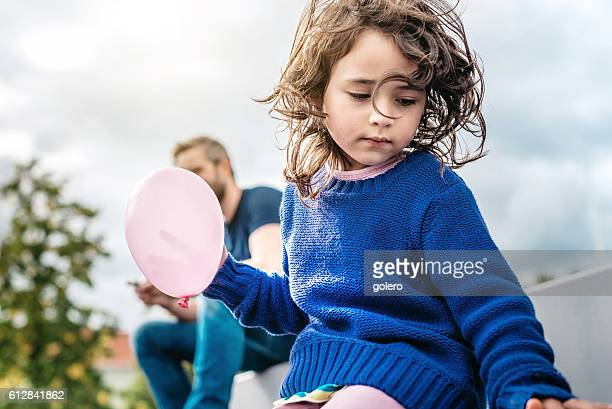 pensive little girl holding pink balloon while father using mobile