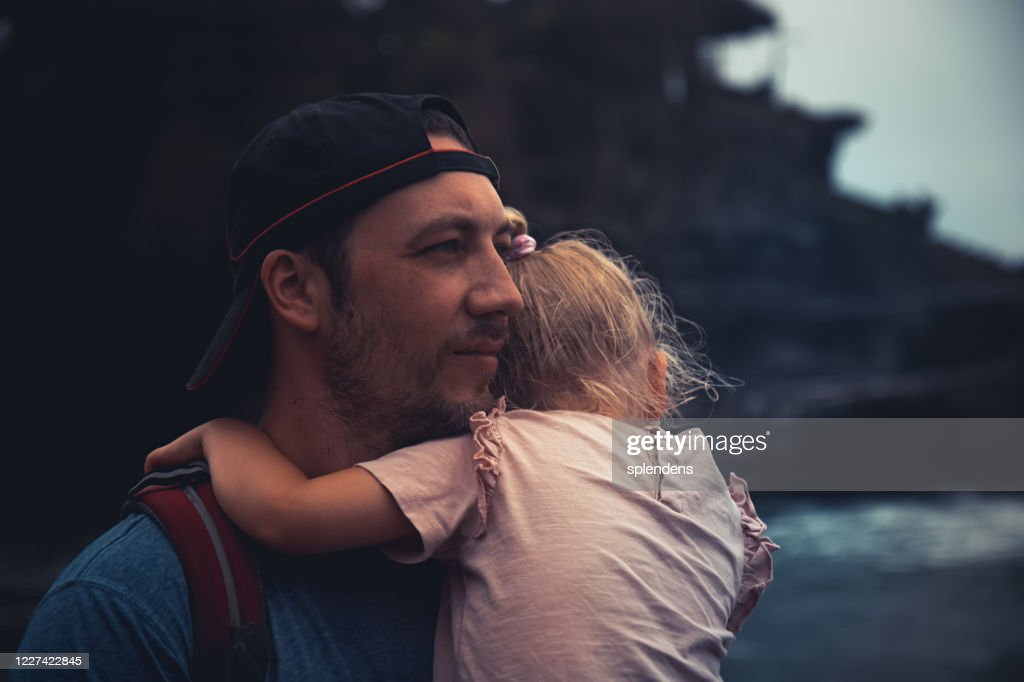 Pensive lonely man father holding child daughter looking with hope into distance in dark vintage style : Stock Photo