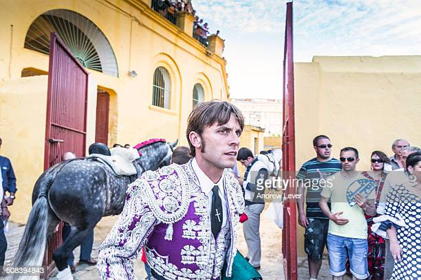 Pensive looking matador wearing a purple jacket prepares for the upcoming bullfight as he walks around at the entrance of the Bullring.