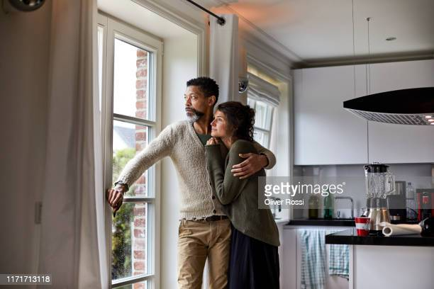 pensive man embracing young woman looking out of window in kitchen - carinhoso imagens e fotografias de stock
