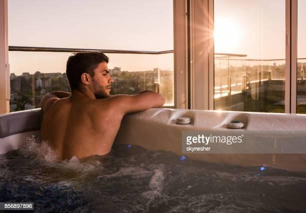 hombre pensativo disfrutando de momentos de relax en un jacuzzi. - darse un baño fotografías e imágenes de stock