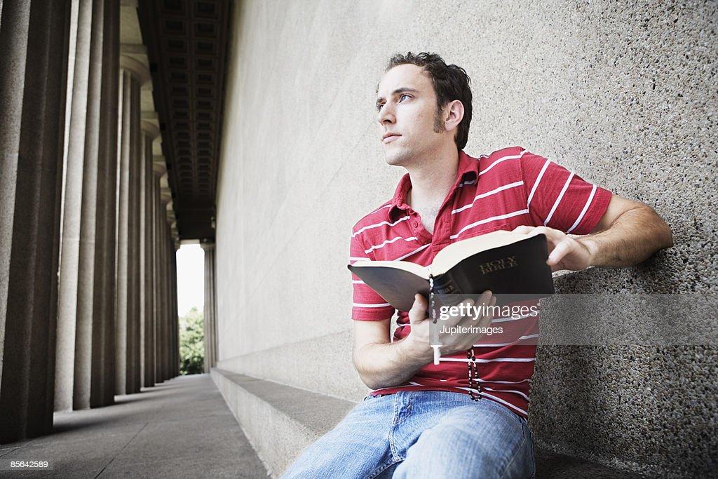 Pensive man holding open bible : Stock Photo