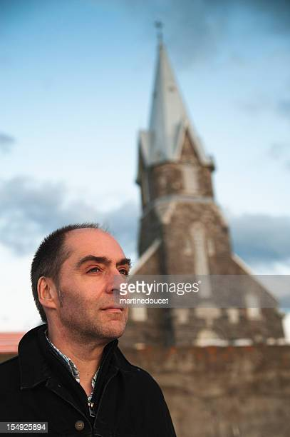 "pensive man in front of church. - ""martine doucet"" or martinedoucet stock pictures, royalty-free photos & images"