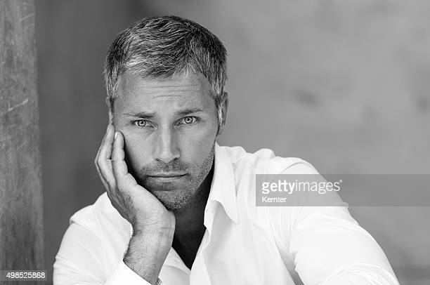 pensive man leaning on his hand - most handsome black men stock photos and pictures