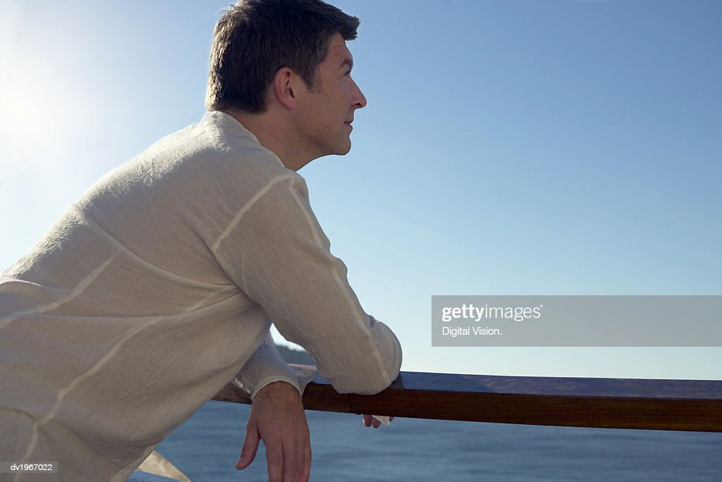 Pensive Man Leans on a Railing by the Sea, Looking at the View : Stock Photo