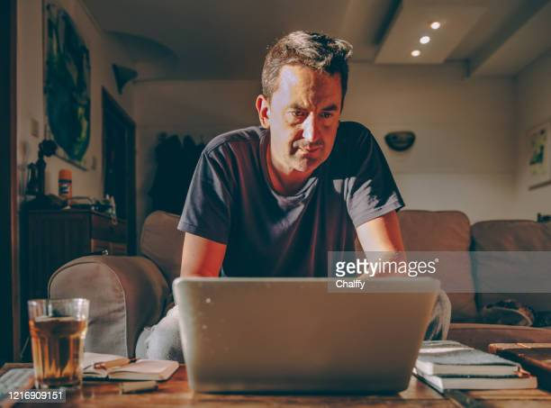 pensive man looking at laptop while working at home - one mature man only stock pictures, royalty-free photos & images