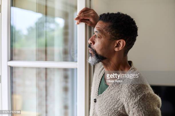 pensive man looking out of window - quarantäne stock-fotos und bilder