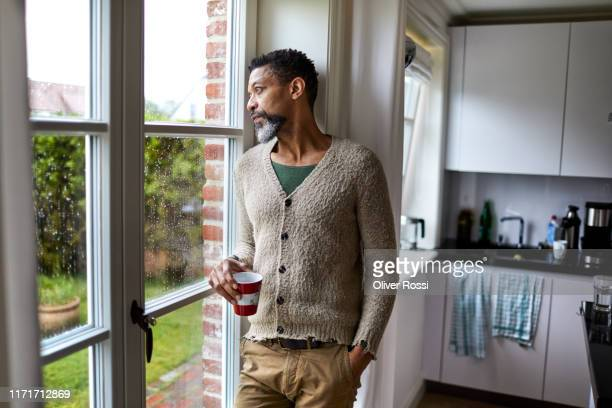 pensive man looking out of window - cardigan sweater stock pictures, royalty-free photos & images