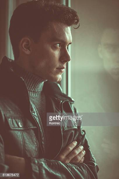 Pensive man looking through window on rainy day