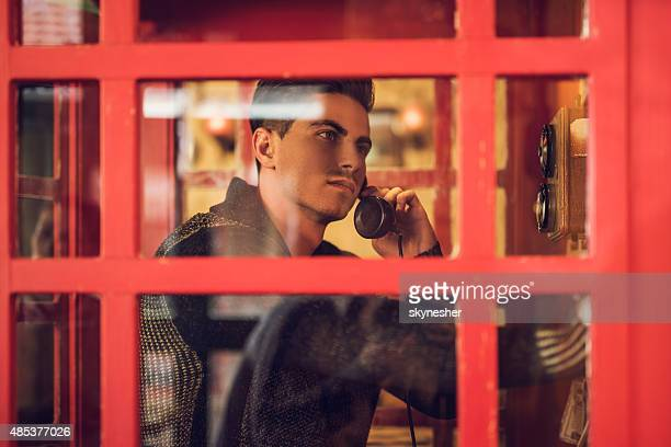 Pensive man making phone call from call box.