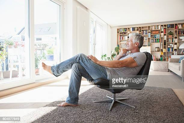 Pensive man relaxing on leather chair at home looking through the window
