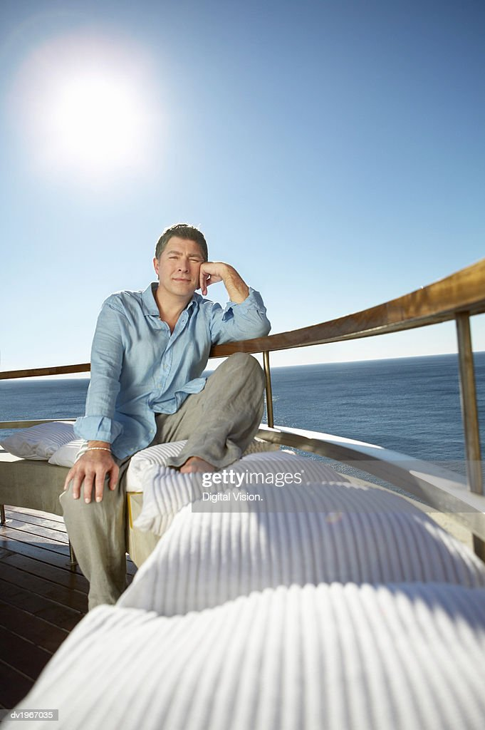 Pensive Man Sits on a the Bench of a Sunny Balcony : Stock Photo