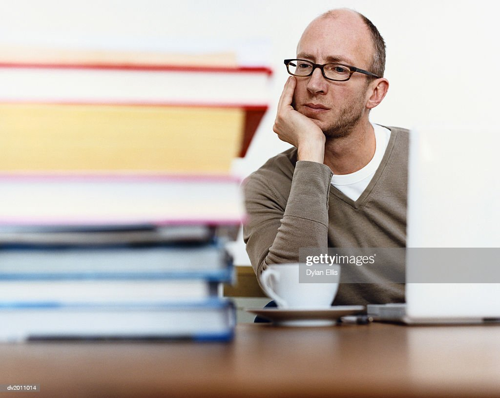 Pensive Man Sitting at a Table, Pile of Books in the Foreground : Stock Photo