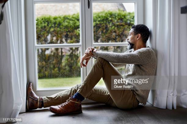 pensive man sitting on the floor looking out of window - depression sadness stock pictures, royalty-free photos & images