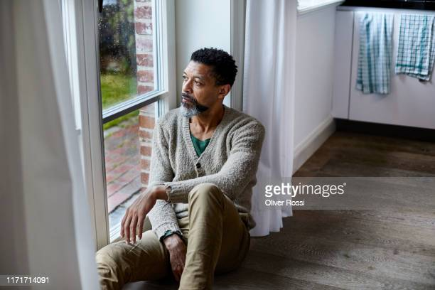 pensive man sitting on the floor looking out of window - despair stock pictures, royalty-free photos & images