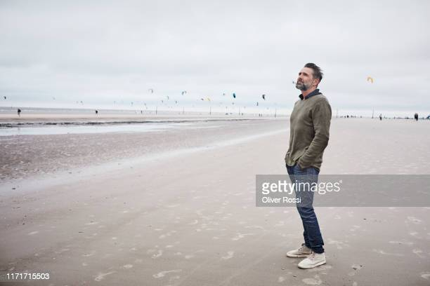 pensive man standing on the beach - ein mann allein stock-fotos und bilder