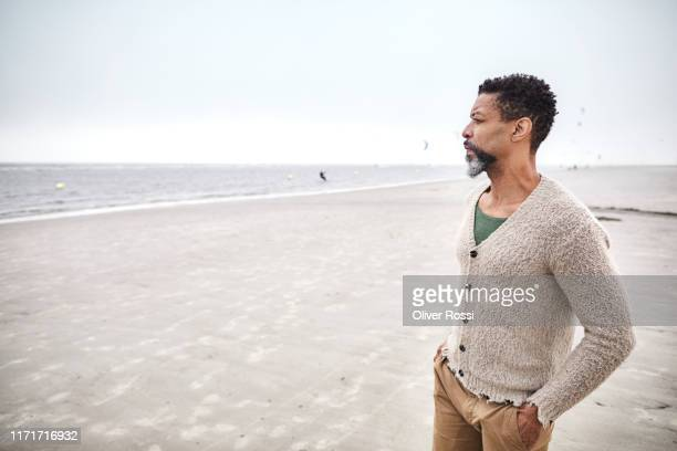 pensive man standing on the beach - 50 54 years stock pictures, royalty-free photos & images