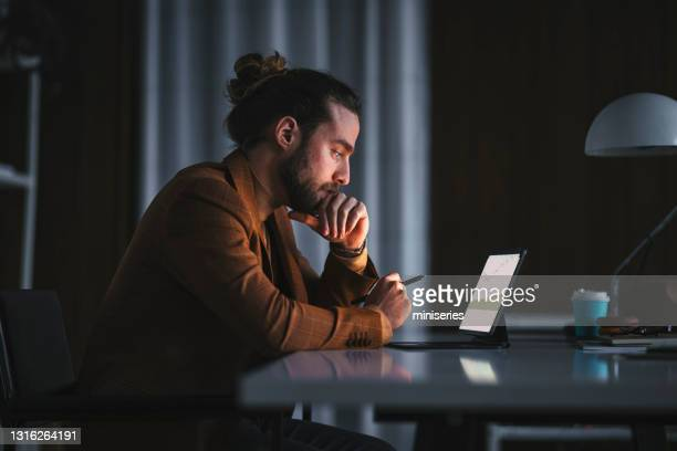 pensive man working on laptop in office - economist stock pictures, royalty-free photos & images