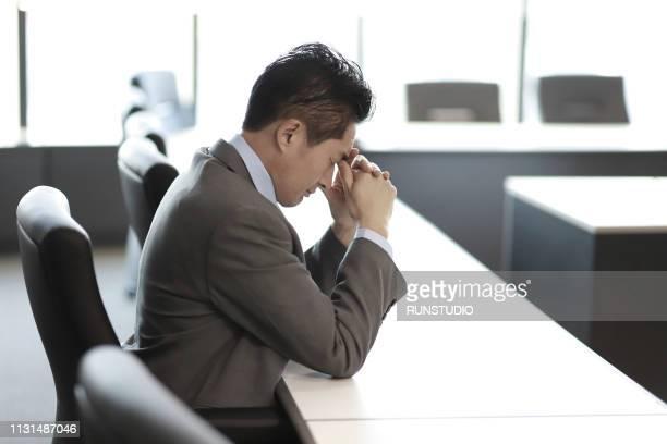 pensive mature businessman at desk - 中年の男性一人 ストックフォトと画像