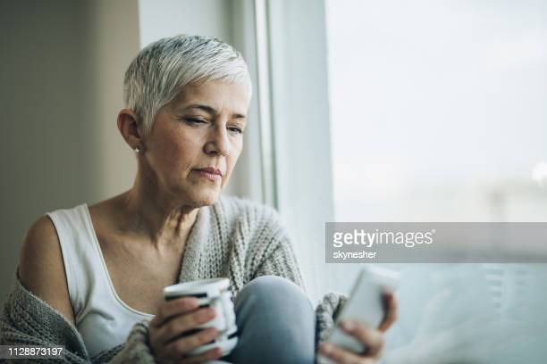 pensive mature woman reading text message on cell phone by the window. - introspection stock pictures, royalty-free photos & images