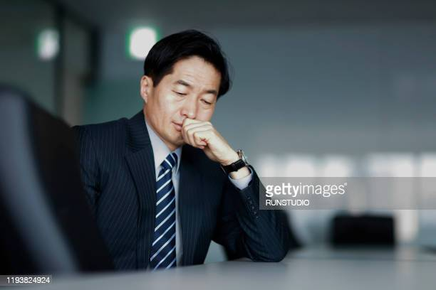 pensive middle aged businessman with hand on chin in office - 中年の男性一人 ストックフォトと画像