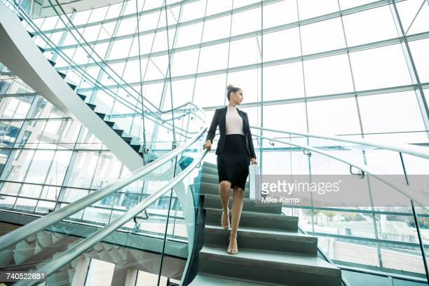 pensive mixed race businesswoman descending staircase - low angle view stock pictures, royalty-free photos & images
