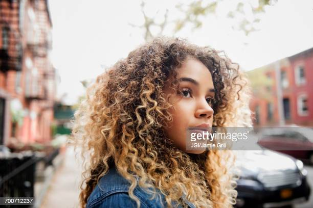 pensive mixed race woman in city - femme brune de dos photos et images de collection