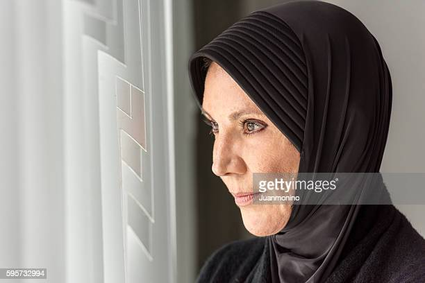 Pensive Muslim Woman looking through a Window