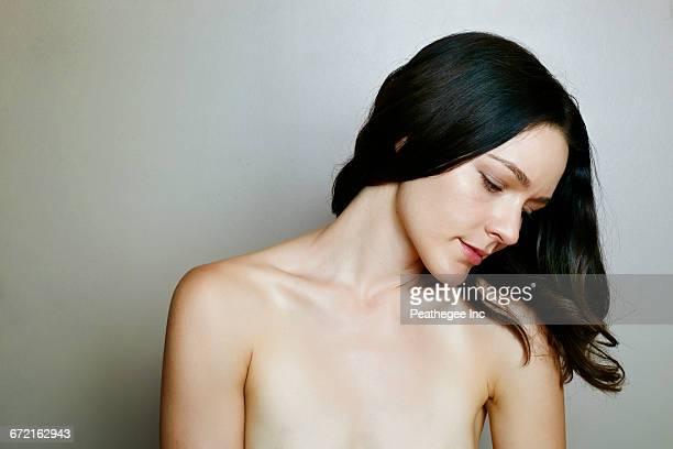 pensive naked caucasian woman near wall - romp lichaamsdeel stockfoto's en -beelden