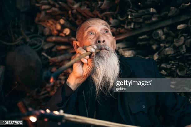 pensive old chinese senior man smoking pipe - tradition stock pictures, royalty-free photos & images