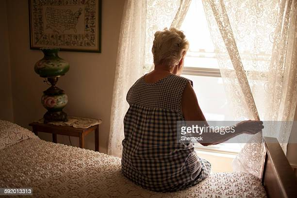 pensive older woman looking out bedroom window - loneliness stock pictures, royalty-free photos & images