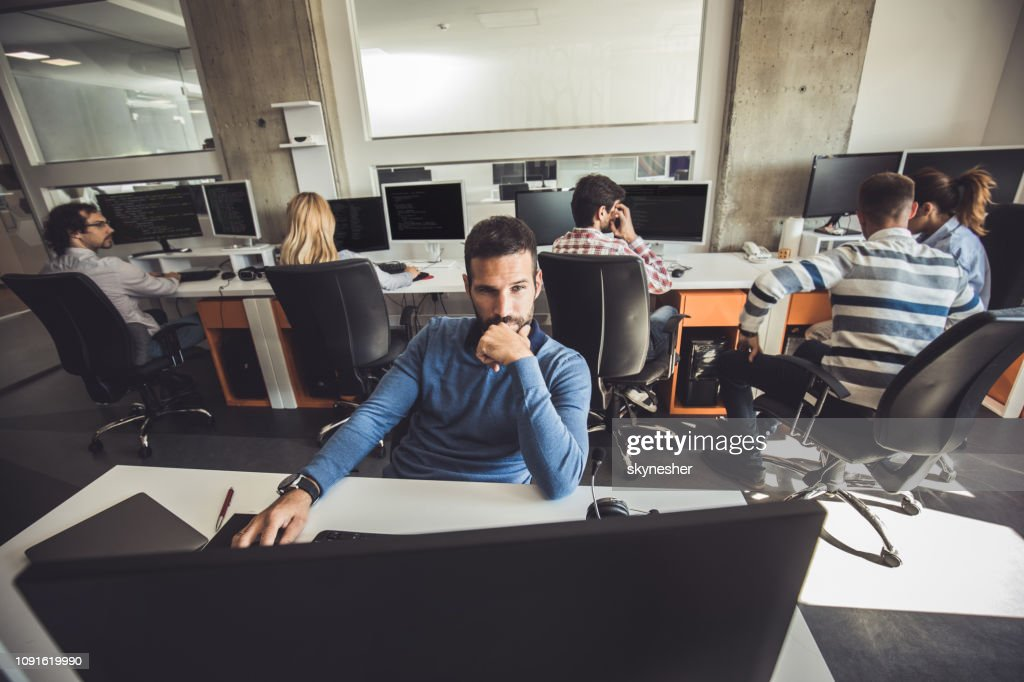 Pensive programmer working on PC in the office full of people. : Stock Photo