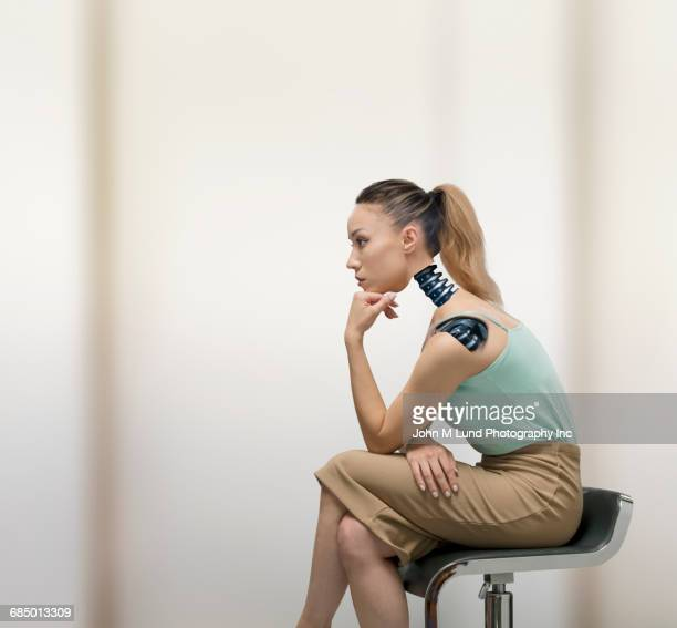Pensive robotic Mixed Race businesswoman sitting on chair