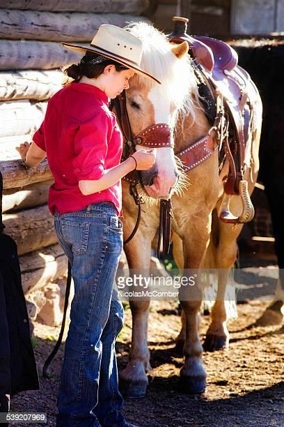 Pensive sad ranch employee strokes horse for comfort