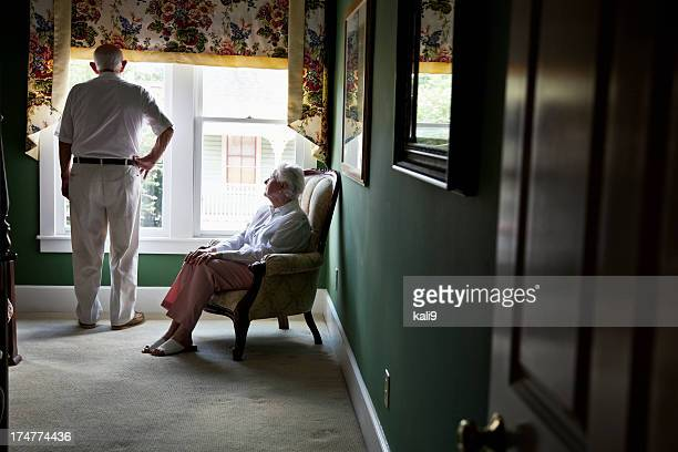 Pensive senior couple looking out window