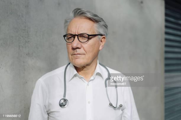 pensive senior doctor at a concrete wall - wegsehen stock-fotos und bilder