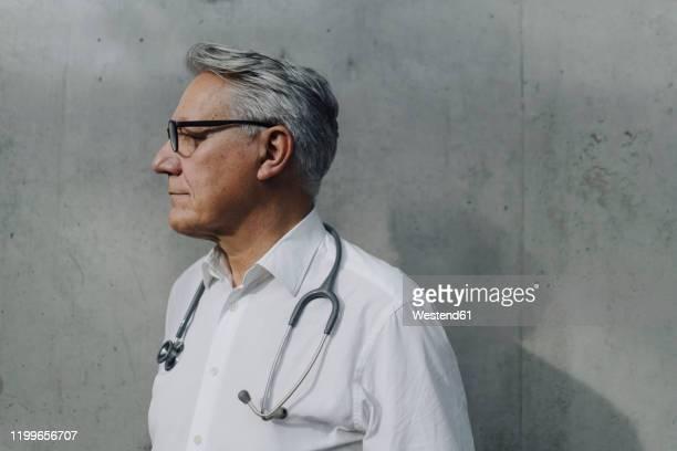 pensive senior doctor at a concrete wall - vista de costado fotografías e imágenes de stock