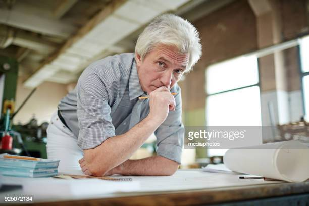 Pensive senior engineer working with blueprint